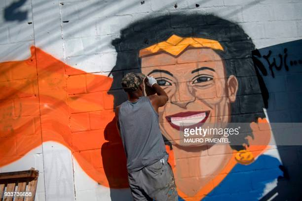 A man paints a mural depicting Brazilian slain human rights activist and politician Marielle Franco as Wonder Woman as about 2000 people march in her...