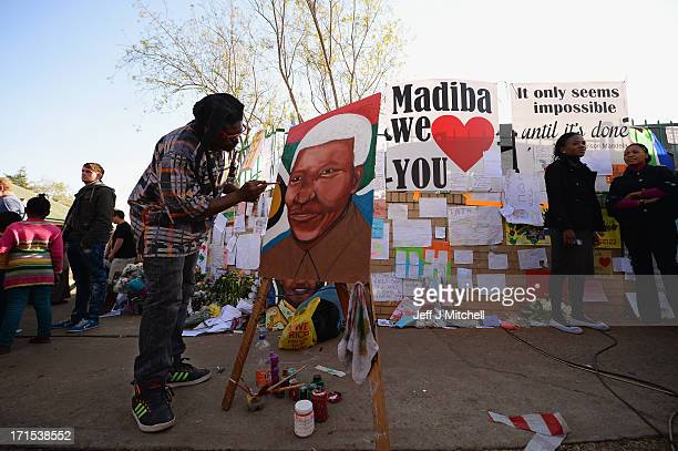 A man paints a picture as people gather to leave messages of support for former South African President Nelson Mandela outside the Mediclinic Heart...