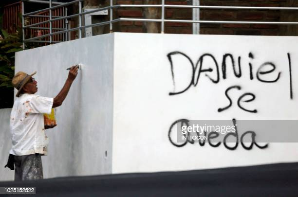 A man paints a wall next to a graffiti reading Daniel stays referring to Nicaraguan President Daniel Ortega during the commemoration of the 51st...