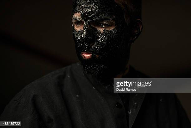 A man paints his face with oil and soot as he dresses up as a devil to join a carnival festival on February 14 2015 in Luzon Spain Every year Luzon...
