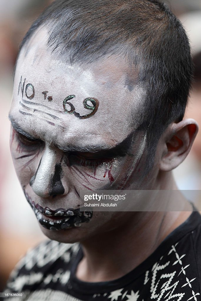 A man paints his forehead 'No To 6.9' during a protest against the government's White Paper on Population and labour-related matters that affect Singaporeans at Speakers' Corner in Hong Lim Park on May 1, 2013 in Singapore. Thousands of protesters gathered today in an inaugural labour day protest against the 6.9 million population government white paper that revealed it could increase 30% to 6.9 million by 2030, angering residents who already see a strain on housing, transportation and healthcare. This is a follow up protest after one was held on 16 Feb, 2013 organised by the same organiser, transitioning.org