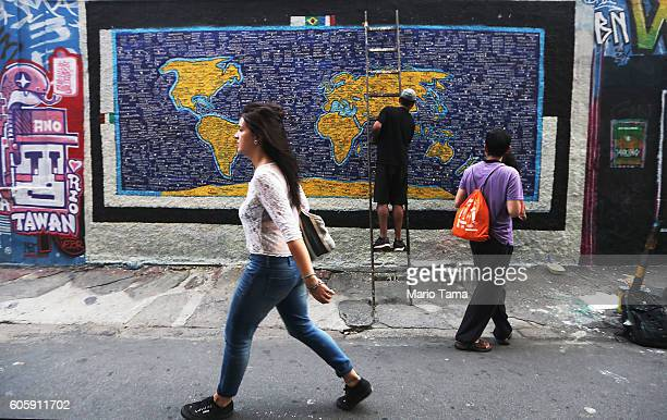 A man paints street art depicting a world map in the Lapa neighborhood on September 15 2016 in Rio de Janeiro Brazil The city is currently hosting...