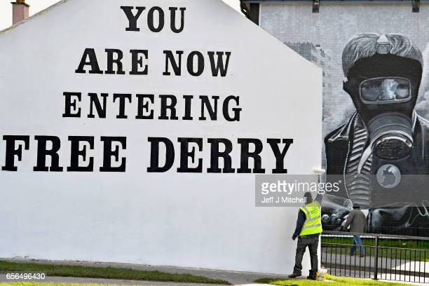 A man paints the 'Free Derry' corner wall in the Bogside ahead of the Funeral of Martin McGuinness on March 22 2017 in Belfast Northern Ireland...