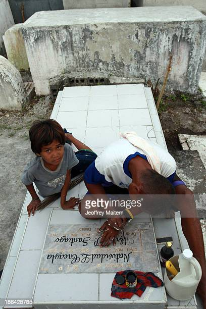 A man paints the tomb of a departed loved one ahead of All Saints' Day tomorrow on October 31 2013 in Cotabato City Philippines As the largest...