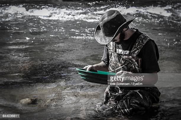 man panning for gold at lake - gold rush stock photos and pictures
