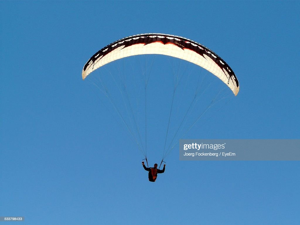 Man Paragliding Against Clear Blue Sky : Foto stock