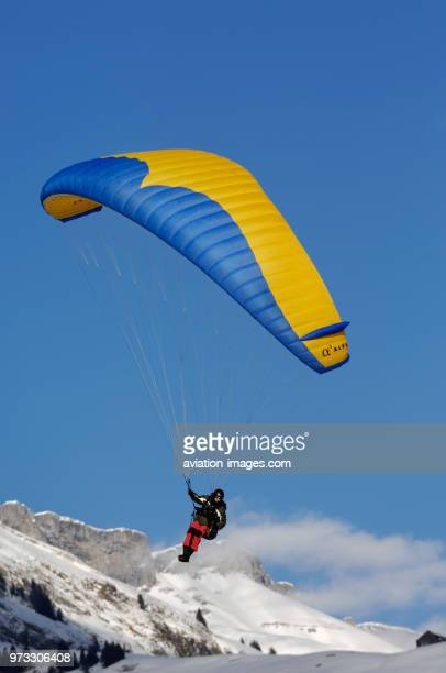 man paragliding an A2 Alpha with snow mountains and clouds behind