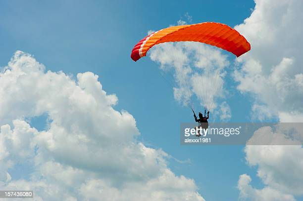 A man paragliding in the blue sky