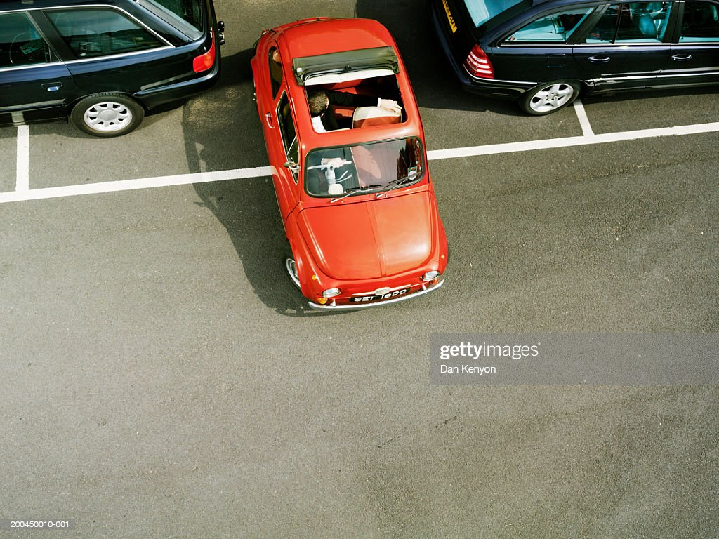 Man parking red car, overhead view : Stock-Foto