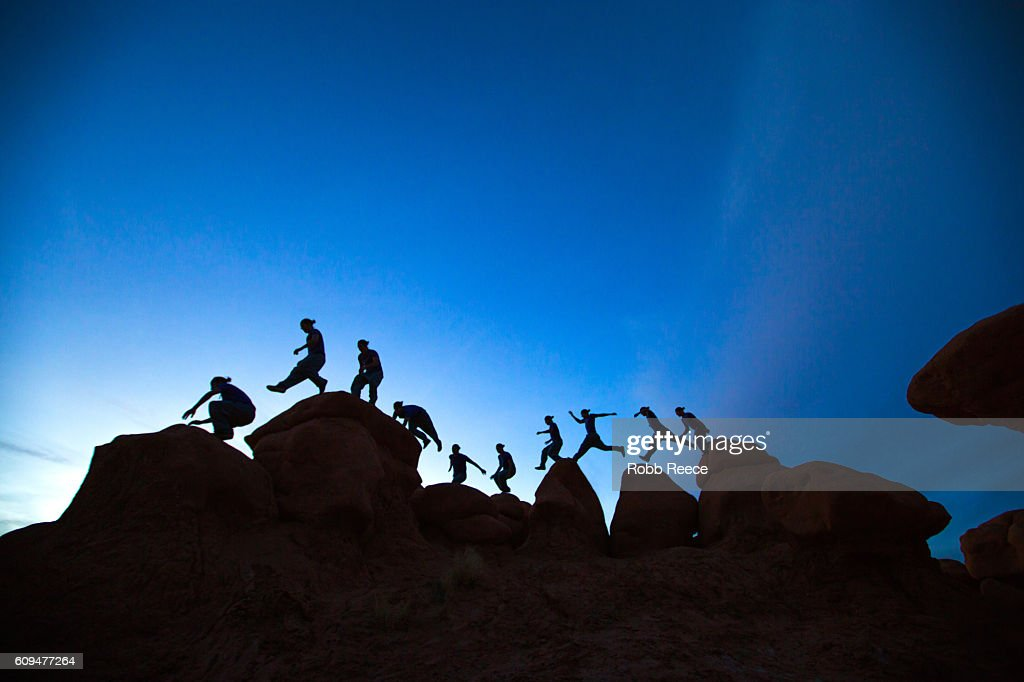 A man parkour running outdoors on rock formations in the desert : Stock Photo