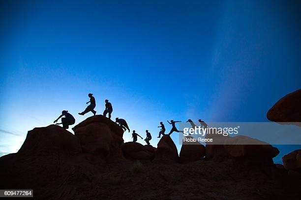a man parkour running outdoors on rock formations in the desert - robb reece stock photos and pictures