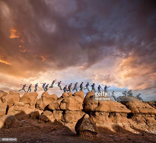 a man parkour running outdoors on rock formations in the desert - robb reece fotografías e imágenes de stock