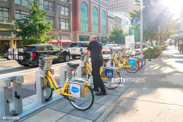 Man parks bicycle at a bike sharing station in downtown Indianapolis Indiana USA