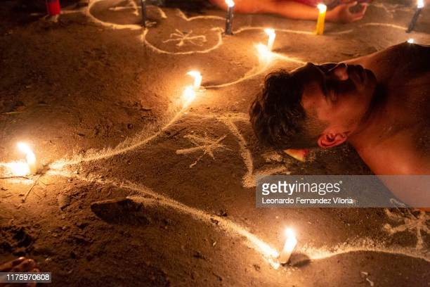 Man participates in a healing ritual called Velación at night during a spiritual ritual in a portal in the mountain of Maria Lionza at Sorte on...