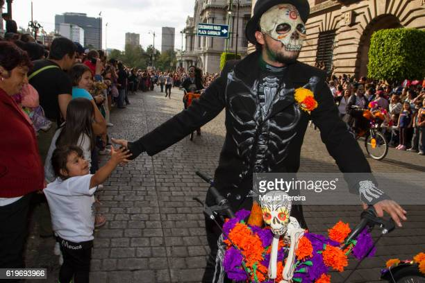 A man participating in the parade during the Day of the Dead Celebrations in Mexico City shared hand with a boy in the crowd as he enters into the...