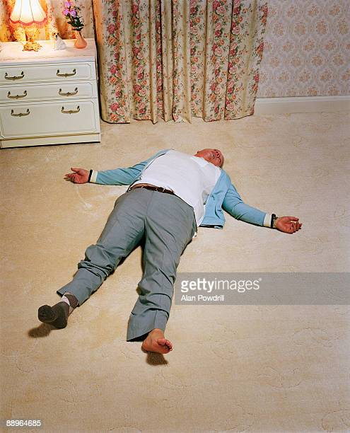 man passed out on carpet with one sock - dead body stockfoto's en -beelden