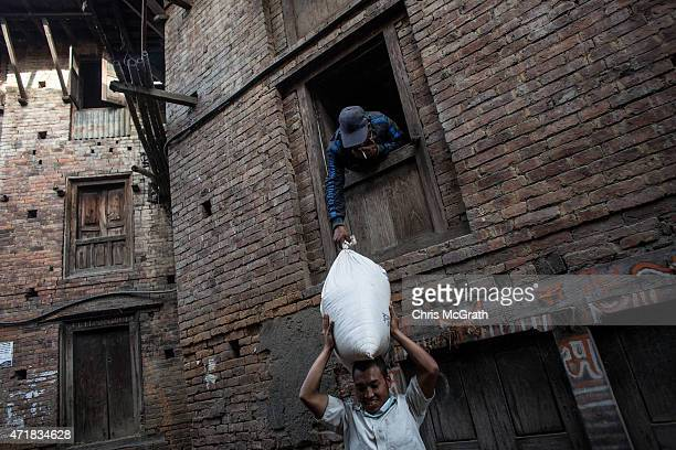 A man passes a bag of rice out of the second storey window of his damaged storeroom shophouse in Bhaktapur on May 1 2015 in Kathmandu Nepal A major...