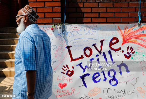 A man passes a banner covered in tributes outside Finsbury Park Mosque near to the scene of the June 19 van attack on pedestrians in the Finsbury...