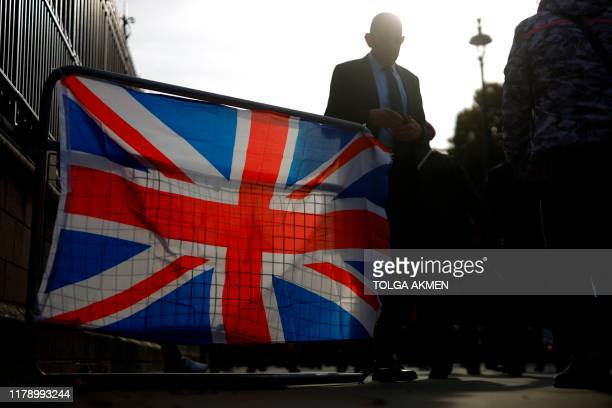 A man passes a barrier decorated with a Union Flag outside the Houses of Parliament in London on October 30 2019 Britain's political leaders tested...