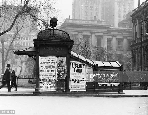 A man passes a boy as he walks towards a subway entrance kiosk which bears signs for the Third Liberty Loan New York Spring 1918 One poster reads...