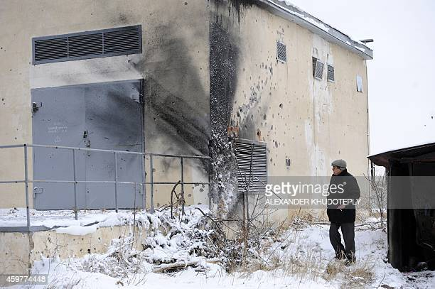 A man passes a building injured as a result of night shelling between Ukrainian forces and proRussian separatists in the eastern Ukrainian city of...