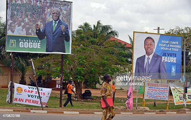 A man passes a campaign sign for current Togolese President Faure Gnassingbe and opponent Tchaboure Gogue in Lome on April 23 2015 Gnassingbe is...
