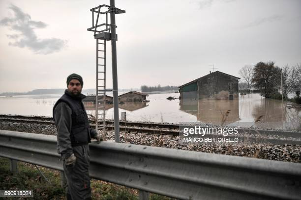 A man passes a flooded area in Brescello on December 12 after the Enza river broke its banks following heavy rain throughout the northern Italy...