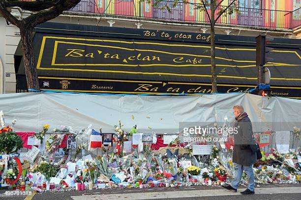 A man passes a memorial with flowers and candles in front of the Bataclan concert hall on November 26 left in memory for the victims of the November...