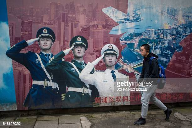 A man passes a military propaganda poster in Shanghai on March 5 2017 / AFP PHOTO / Johannes EISELE