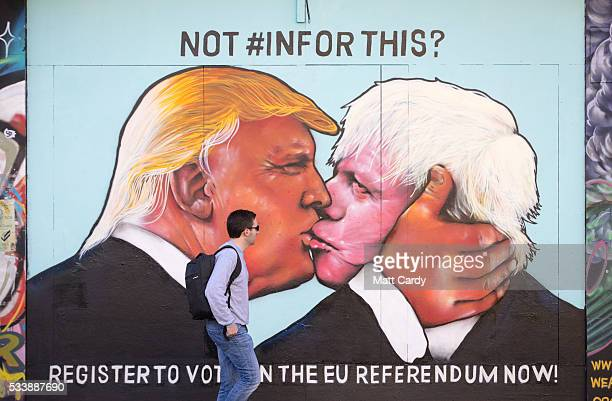 A man passes a mural that has been painted on a derelict building in Stokes Croft showing US presidential hopeful Donald Trump sharing a kiss with...