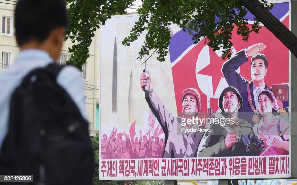 A man passes a nationalist billboard on a street in Pyongyang on Aug 16 as tensions linger between North Korea and the United States over Pyongyang's...