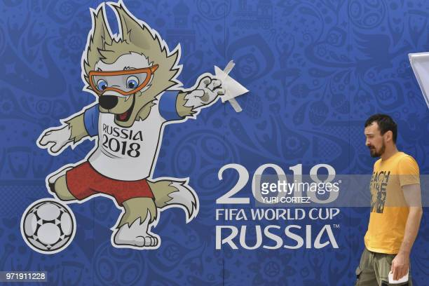 A man passes a poster featuring Zabivaka the official mascot of the Russia 2018 World Cup football tournament outside the 80000seater Luzhniki...
