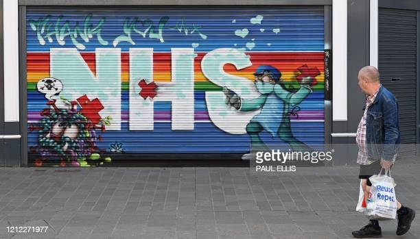 Man passes a street art graffiti mural in support of the NHS on the shutters of a closed-down shop in Hull, northern England on May 9 as life in...