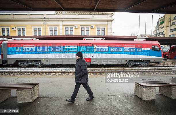 A man passes a train bound for Kosovo at the main railway station in Belgrade on January 14 2017 A train from Russia decorated with the Serbian flag...