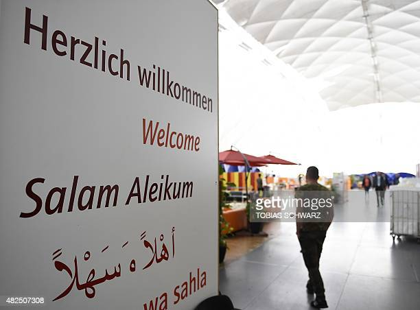 Man passes a welcome sign inside an air-inflated tent serving as first registration centre for refugees in Berlin's Moabit district on July 31, 2015....