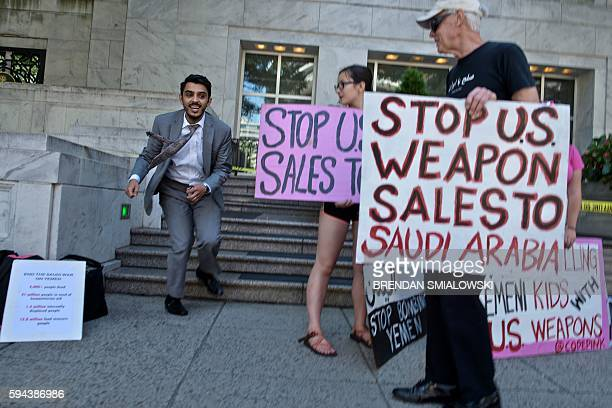 A man passes activists during a protest of Saudi military involvement in Yemen outside the embassy of Saudi Arabia on August 23 2016 in Washington DC...