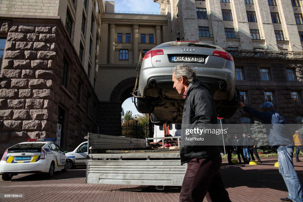 A man passes an evacuated foreign-registered vehicle near Kyiv City Hall at Khreshchatyk street in Kyiv, Ukraine, October 10, 2017.