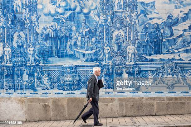 Man passes azulejos Portuguese blue and white wall tiles of Capela das Almas de Santa Catarina St Catherine's Chapel in Porto Portugal