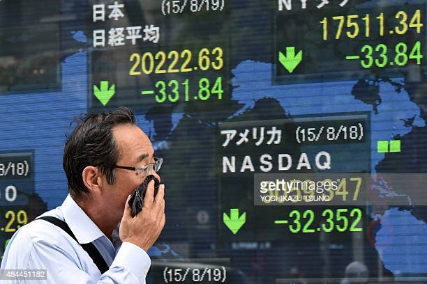 A man passes before a share prices board in Tokyo on August 19 2015 Japan's share prices fell 33184 points to close at 2022263 points at the Tokyo...