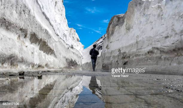 A man passes between the snow cleared SrinagarLeh highway on May 12 2017 in Zojila 108 km east of Srinagar the summer capital of Indian administered...