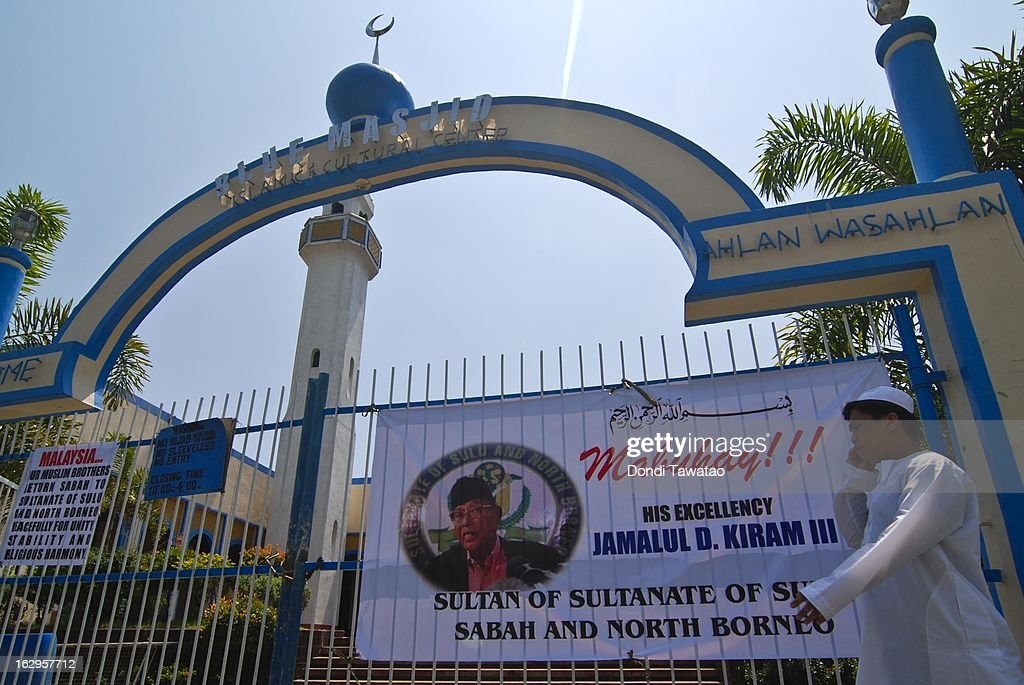 A man passes by a banner featuring self-proclaimed Sulu Sultan Jamalul Kiram III outside a mosque on March 2, 2013 in Manila, Philippines. President Benigno Aquino III has urged followers of Jamalul Kiram III to surrender and come out of hiding in the village of Lahad Datu, Sabah. Malaysian Prime Minister Najib Razak has warned he will take action against the group, which were involved in a shoot-out with Malaysian police that killed two Malaysian police commandos and left 12 followers of Kiram dead. (Photo by Dondi Tawatao/Getty