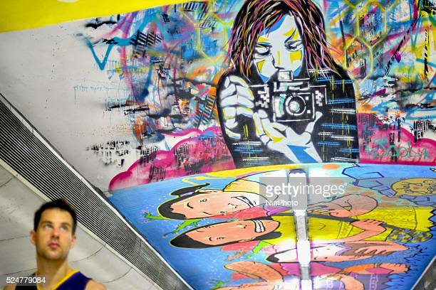 A man passes by a colourful mural painted along the ceiling of a pedestrian underpass in the financial district of Makati Metro Manila Philippines...
