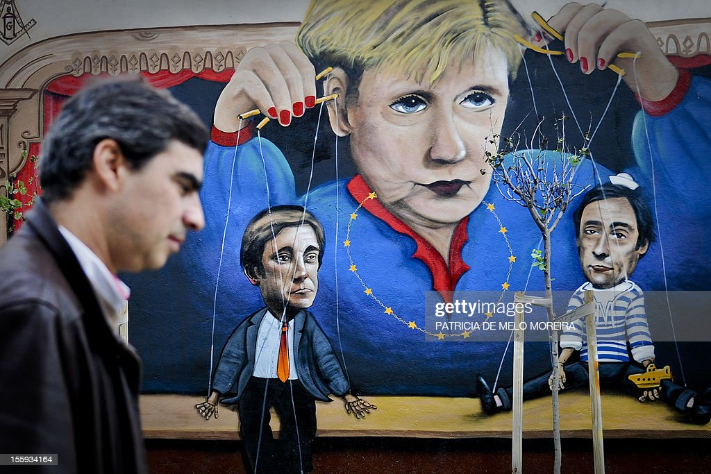 A man passes by a graffiti depecting German Chancellor Angela Merkel handling string puppets of Portuguese Prime Minister Pedro Passos Coelho (L) and Portugal's Foreign Minister Paulo Portas (R) in Lisbon on November 9, 2012. German Chancellor Angela Merkel will visit Lisbon on November 12, 2012.