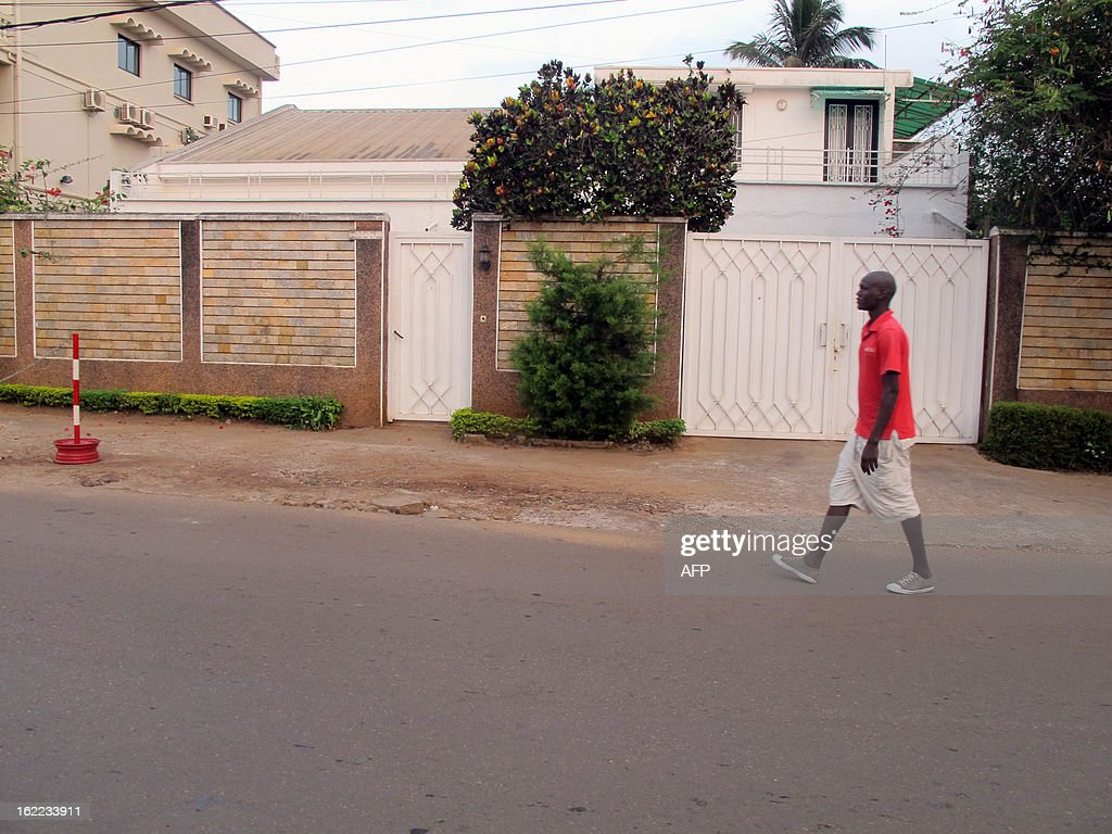 A man passes by a house on February 21, 2013 in the Bastos district of the Cameroonian capital Yaounde, where live seven members of a French family who were seized in a kidnapping allegedly carried...