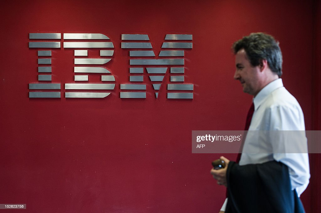 A man passes by a logo at IBM office in Hortolandia, about 100km north from Sao Paulo, Brazil on September 14, 2012. AFP PHOTO/Yasuyoshi CHIBA