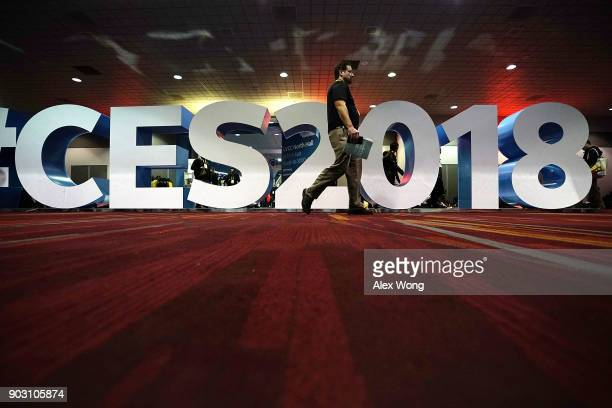A man passes by a sign for the show during CES 2018 at the Las Vegas Convention Center on January 9 2018 in Las Vegas Nevada CES the world's largest...