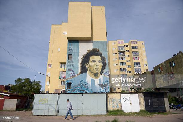 A man passes by a wall painted with a portrait of Italian Juventus FC player Argentinian Carlos Tevez in Barrio Ejercito de los Andes better known as...