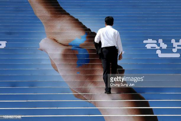 A man passes by an image of two hands shaking to form the shape of the Korean Peninsula to support the upcoming interKorean summit on September 17...