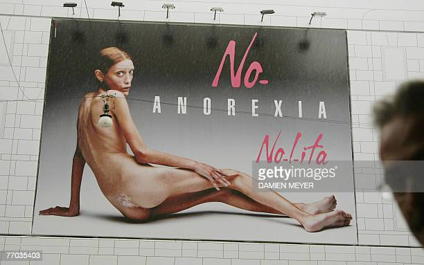 A man passes by an italian advertising campaign featuring the photo of an emaciated girl 26 September 2007 in Milan in the middle of Milan fashion...