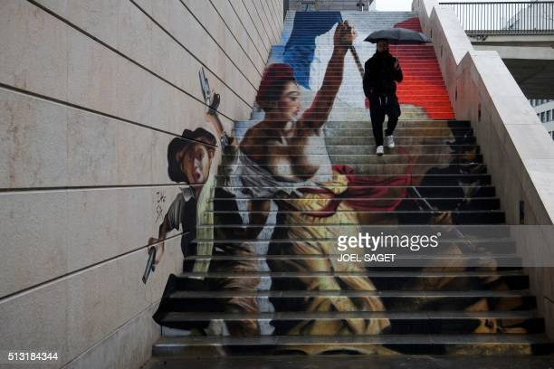 A man passes by an unfinished street art graffiti made in a stairway by French street artists Zag and Sia in Paris on March 1 2016 The two artists...
